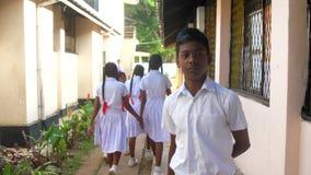 Sinhalese boys and girls walk between buildings. Colombo/Sri Lanka - April 05 2019: Sinhalese boys and girls in uniforms walk along thin road between school stock footage
