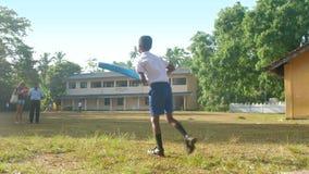 Sinhalese schoolboy holds blue cricket bat and runs. Colombo/Sri Lanka - April 05 2019: Sinhalese schoolboy holds blue cricket bat and runs on school playground stock video footage