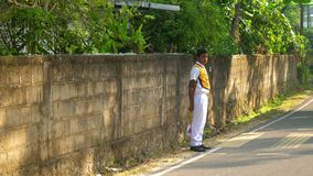 Sinhalese schoolboy stands at grey asphalt road slow. Colombo/Sri Lanka - April 05 2019: Sinhalese schoolboy stands at grey asphalt road holding small sign in stock footage