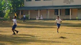 Sinhalese schoolboys run on playground lit by sun. Colombo/Sri Lanka - April 05 2019: Sinhalese schoolboys play cricket and run on playground lit by autumn sun stock footage