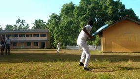 Sinhalese schoolboys in white uniform play cricket. Colombo/Sri Lanka - April 05 2019: Sinhalese schoolboys in white uniform play cricket on green playground stock video