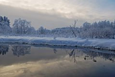 Sinialliku小河在一个冷的冬日,多雪的树和多云天空在水中反射 免版税库存图片