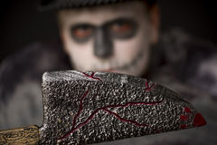 Sinister bloodied Halloween meat cleaver. Sinister wooden bloodied Halloween meat cleaver held in the darkness by a man in ghoulish skull makeup, focus to the royalty free stock photo