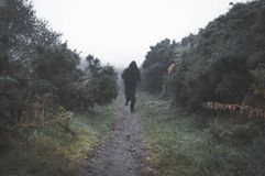A sinister blurred hooded figure running towards the camera on a country path on a foggy rainy day. With a muted, dark edit.  stock images