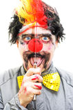 Sinister Clown. Holds Up A Knife Vertical To His Face While Opening His Mouth In A Creepy Isolated Expression Royalty Free Stock Photos