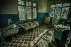 Sinister and creepy old laundry room in an abandoned psychiatric hospital Royalty Free Stock Photo