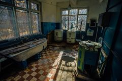 Creepy old laundry room with a dirty floor and broken wash machines and bathes in an abandoned psychiatric hospital. Royalty Free Stock Photography