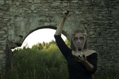 Sinister female ritual. Witch - young woman in black dress with ominous make-up conducts some sinister pagan rite among ancient ruins royalty free stock images