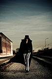 Sinister Figure Near Railroad Tracks. Scary looking woman in striped pants walking beside railroad tracks Royalty Free Stock Images