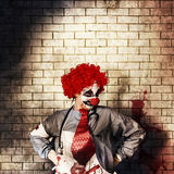Sinister gothic clown standing on grunge brickwall. Sinister gothic hospital clown standing on grunge brick wall with masthead copy space. Psychopath surgeon Royalty Free Stock Photos