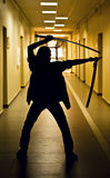 Sinister image of a blade. Silhouette of a man with a sword in a dark hallway. Corridor filled with yellow light, face and body of a man is not visible, you can Royalty Free Stock Photography