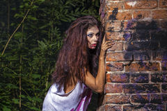 Sinister sexy woman in a bloody shirt on dark brick wall Stock Images