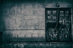 Sinister urban background of old abandoned building. Giant door of old abandoned building with downed wire of street light. Empty dark wall. Sinister urban Stock Photography