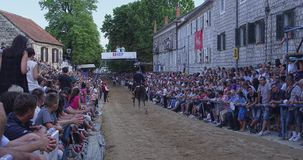 Sinj Alka racecourse. SINJ, CROATIA - August 3, 2014: Alkar riding by the people in the stands during Alka, traditional knight game in memory of victory against stock footage