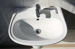 Sink. Ceramic white washing sink with a modern faucet stock images