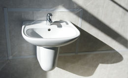 Sink. Ceramic white washing sink with a modern faucet stock image
