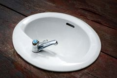 Sink. Close up of modern sink on Wood backgroundin the bathroom stock photo