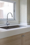 Sink and faucet on white counter in kitchen room Stock Photography