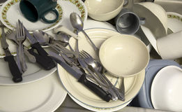 Sink full of dirty tableware. A variety of plates, cups, bowls, and silverware arranged in a sink as a background Stock Photography