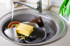 Sink full of washing dishes. Filled with dish soap water Stock Photo