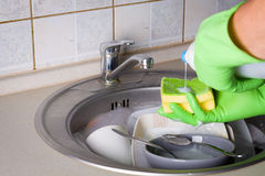 Sink full of washing dishes. Filled with dish soap water and hands in green gloves Stock Photography