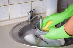 Sink full of washing dishes. Sink full of washing dishes filled with dish soap water and hands in green gloves Stock Images