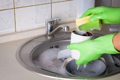 Sink full of washing dishes. Filled with dish soap water and hands in green gloves Royalty Free Stock Photo