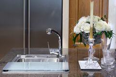 Sink with glass and candlestick on marble table in modern kitche Stock Photo