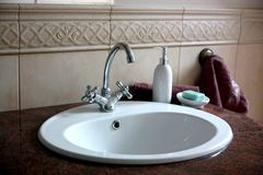 Sink in the marble countertop. In the bathroom Stock Images