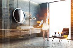 Sink and mirror in bathroom, armchair, woman. Woman in bathroom corner with concrete walls, wooden floor and white angular sink standing on wooden countertop stock images
