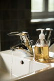 Sink with runnig water and liquid soap dispenser Stock Photos
