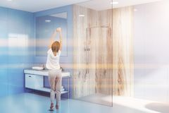 Sink and shower in blue bathroom corner, woman. Woman in modern bathroom with blue walls, white floor, glass and wooden shower and white sink standing on white royalty free stock photos