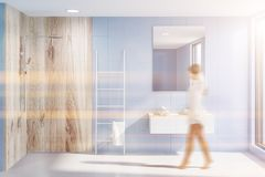 Sink and shower in blue bathroom, ladder, woman. Woman in modern bathroom with blue walls, white floor, sink with white countertop under it and vertical mirror stock photos