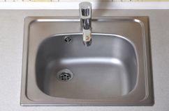 Sink with silver faucet. New equipment in kitchen counter stock photo