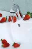 Sink with strawberries. Sink with running water lined with  strawberries Stock Photography