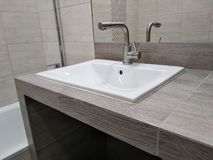 Sink on the table top of drywall and tiled, handmade. ease of use bathroom. niche in the countertop for a drawer with cosmetics stock photo
