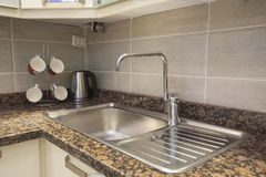 Sink and tap with kettle in apartment Royalty Free Stock Photos
