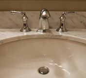 Sink and taps. Bathroom sink and taps on marble countertop Royalty Free Stock Photo