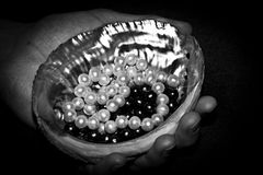 Sink and the white and black pearls. In hand Stock Image