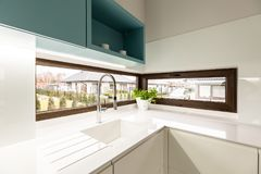 Sink and window. White sink with faucet and big, brown window in kitchen interior royalty free stock images