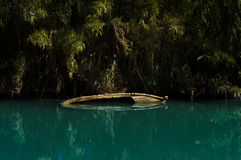 Sinked boat in a river. With tropical colors Royalty Free Stock Photos