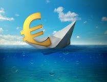 Sinkendes Eurowährungszeichen mit dem Papierboot, das in Ozean schwimmt Stockfotografie