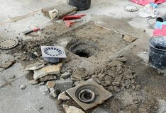 The sinkhole of a patio. A bricklayer arranging the drainage hole of a yard in house Stock Photo