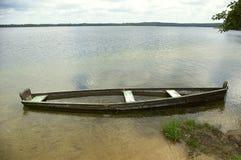 Sinking boat. Half sunk old boat at lake shore Stock Image