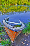 Sinking boat ashore the pond Royalty Free Stock Photo