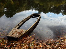 Sinking boat on lake. In the autumn forest Stock Photo