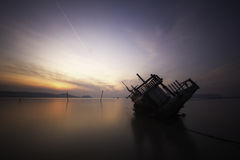 Sinking boat during sunrise. A sinking boat in the sea during sunrise Stock Image