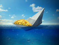 Sinking boat transporting gold symbol of declining commodity prices. Sinking paper boat transporting gold as a symbol of worldwide declining commodity prices Royalty Free Stock Photos
