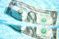 Sinking Dollar. Dollar bill sinking into blue water Stock Image