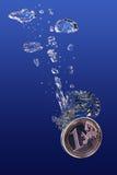 Sinking Euro. One euro coin falling into water Royalty Free Stock Photos